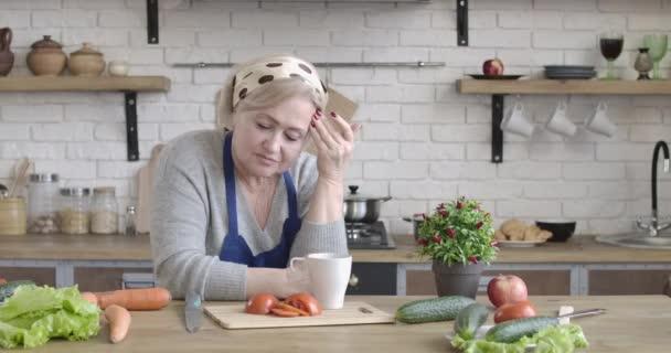 Egy magányos fehér nyugdíjas portréja, aki úgy néz ki, mintha otthon állna a modern konyhában. Depressziós középkorú nő, aki egyedül tölti a nyugdíjas éveit otthon. Szomorúság, életstílus. Cinema 4k ProRes főhadiszállás.