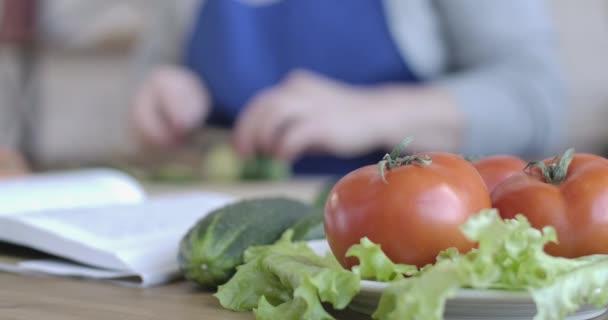 Friss bio zöldségek közelsége az asztalon, amint elmosódott női kezek uborkát vágnak a háttérben. Idősebb kaukázusi nő főz otthon. Vegarianizmus, kaja. Cinema 4k ProRes főhadiszállás.