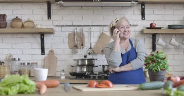 Pozitivní důchodce mluví po telefonu v kuchyni doma. Portrét dospělé veselé bělošky, která stojí uvnitř a povídá si. Vaření, životní styl, volný čas. Cinema 4k ProRes HQ.