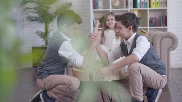 Dva identické dvojčata soupeří v páce a mluví, zatímco jejich mladší sestra jásá v pozadí. Šťastné děti si užívají volný čas doma. Střelba zpoza domu rostliny.