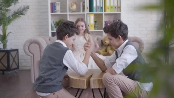 Styloví bělošští chlapci soupeří v páce, jejich veselá sestřička jásá a blíží se objímající roztomilé dvojče. Přátelští sourozenci si užívají čas doma. Radost, štěstí, volný čas.