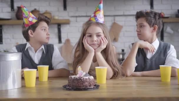 Egy csinos kis szomorú lány portréja, aki az asztalnál ül, ikertestvérekkel, bulikalapban. Ideges fehér srác, aki testvéreivel ünnepli a születésnapját. Szomorúság, család, bulizás.