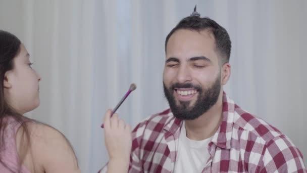 Portrét veselého mladého středovýchodního otce pózujícího pro dceru napodobující aplikaci make-upu. Malá krasavice používající štětec na mužské vousy. Fun, volný čas, životní styl, rodina.