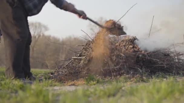 Mature Caucasian farmer throwing dry leaves and branches with shovel into fire outdoors. Environmental problems, anti-ecological way of waste incineration.