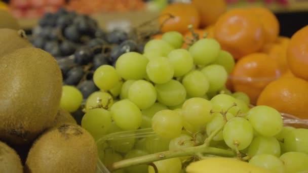 Friss, ízletes zöld szőlő, kivi gyümölcsök és mandarin közeli felvétele az élelmiszerboltban. Ízletes egészséges ételek hevernek a kiskereskedés polcán. Fogyókúra, vitaminok, egészséges táplálkozás.