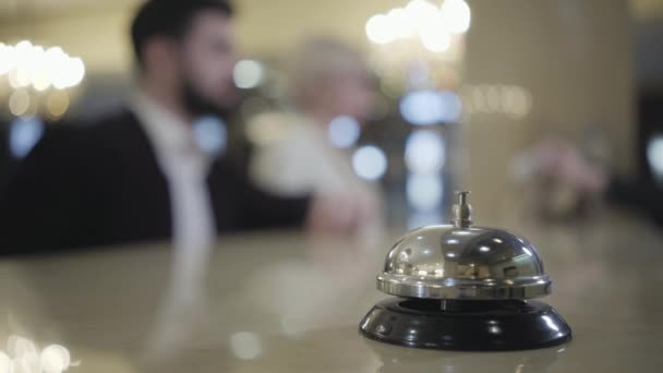 Close-up of vintage hotel bell standing on reception desk as blurred people checking in at the background. Concept of travelling. tourism business, luxury, old-fashioned wealth.