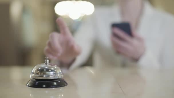 Verschwommene Kaukasierin mit Smartphone, das an der Rezeption Hotelklingeln drückt. Eine unkenntliche Kundin wartet im Vorraum auf die Empfangsdame, um einzuchecken oder auszuchecken. Tourismus, Reisen.