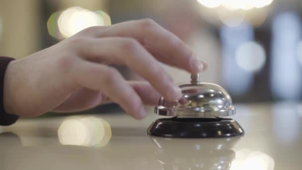 Extrémní detailní záběr neznámého bělocha, jak tiskne hotelový zvon. Nerozpoznatelný mužský klient volá po službě ve vestibulu. Luxus, cestovní ruch, cestování, životní styl.