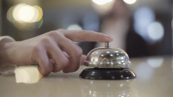 Detailní záběr ženské bělošky, jak tiskne hotelový zvonek. Neznámá klientka volá recepční na recepci. Životní styl, cestování, cestovní ruch.