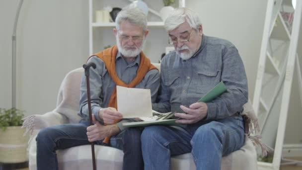 Starší běloch ukazuje staré černobílé fotky kamarádovi v pečovatelském domě. Dva pozitivní zralí důchodci v brýlích sdílení vzpomínek uvnitř.