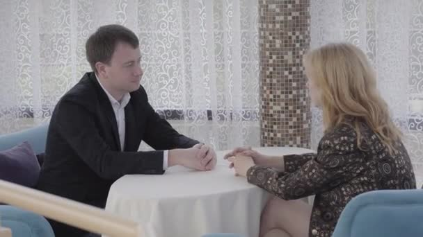 Adult Caucasian man and woman sitting at the table in cozy cafe and talking. Portrait of successful confident people having business meeting in casual atmosphere. Lifestyle, confidence.