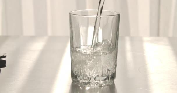 Šumivá voda tekoucí do skla. Neznámý člověk nalévá šumivé nápoje. Zdravý životní styl, izolovaný objekt, zdravotní péče. Cinema 4k ProRes HQ.