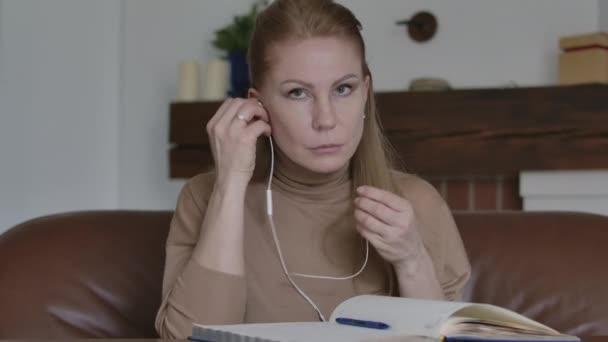 Portrét krásné bělošky, jak si nasazuje sluchátka, mává na kameru a usmívá se. Mladá dáma pozdravuje v online video chatu. Vzdálená práce, obchod, Covid-19 životní styl.