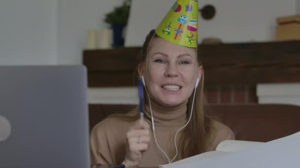 Boldog mosolygós nő parti kalapban nevet és beszél. Egy szőke, örömteli hölgy portréja, aki távolról ünnepel a Covid-19 lezárásán. Elszigeteltség, távoli ünneplés, életmód, öröm, boldogság.