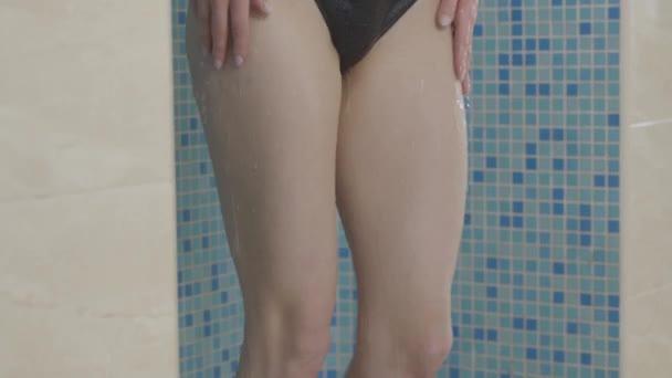 Fényképezőgép halad felfelé gyönyörű test vékony fiatal kaukázusi nő zuhanyozás közben. Portré gyönyörű barna lány fekete bikini mosás uszoda után luxus spa hotel.