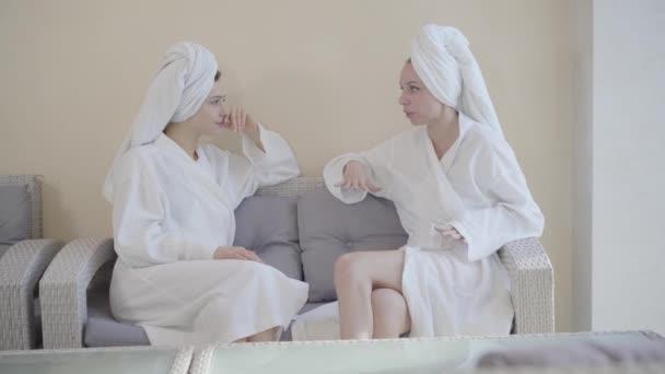 Zwei positive Frauen sitzen auf der Couch im Wellnessbereich und unterhalten sich. Porträt junger kaukasischer Mädchen, die sich um Körper kümmern. Selbstbewusste Damen in Bademänteln und Handtüchern ruhen sich aus. Schönheit, Luxus, Freizeit