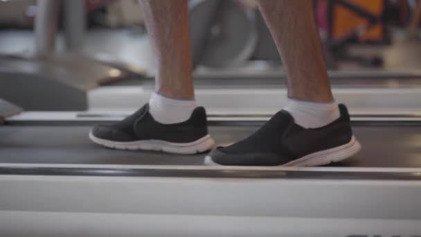 Nahaufnahme männlicher Beine in Turnschuhen, die auf dem Laufband laufen und zu laufen beginnen. Bis zur Unkenntlichkeit erwachsener Typ, der in Turnhallen trainiert. Sport, Fitness, gesunder Lebensstil.
