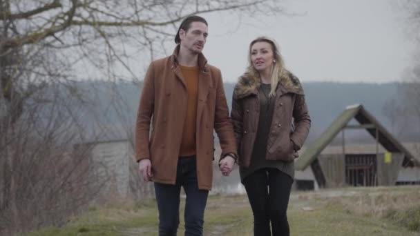 Portrét veselého bělošského páru procházejícího se po venkově a emocionálně si povídajícího. Šťastný bruneta muž a blond žena procházet a mluvit venku. Volný čas, štěstí, životní styl, láska.