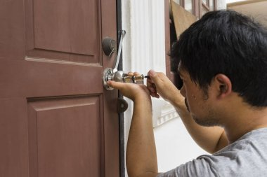 locksmith try to open the old wood door by his tools