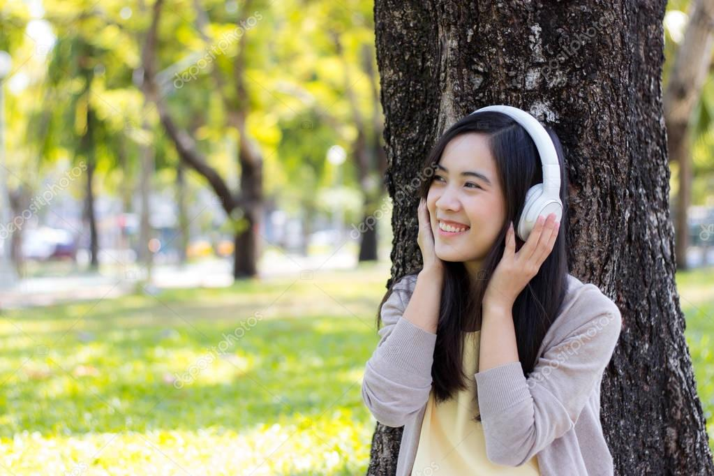 Beautiful asian woman listen to music with white headphone