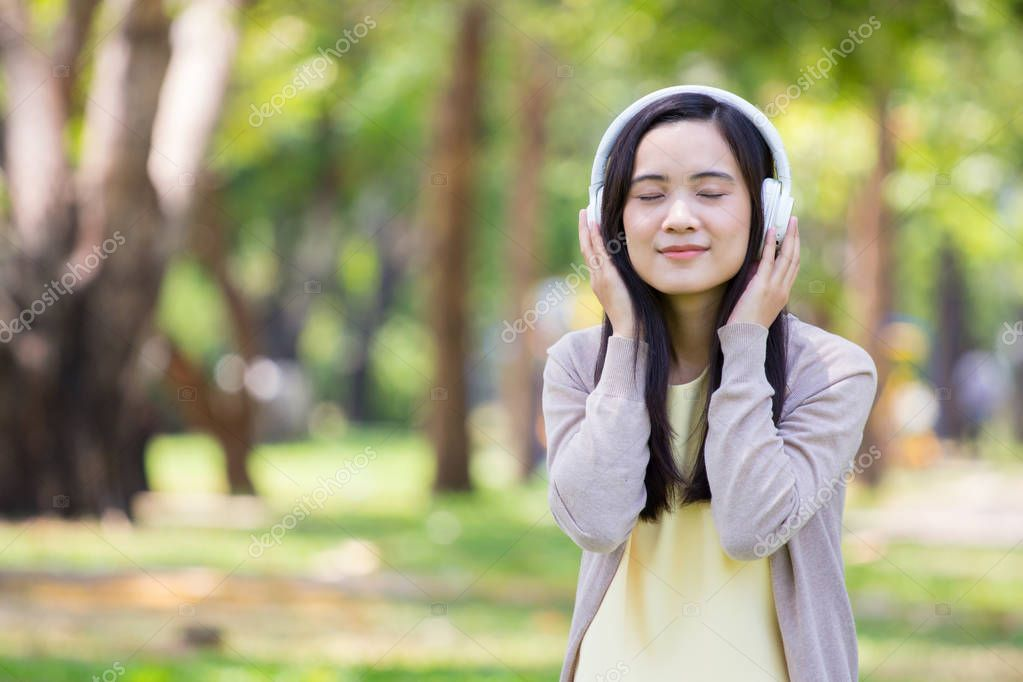 Beautiful asian woman listen to music with white headphone in na
