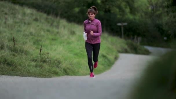 Starší žena běží sám po silnici v woodlands.