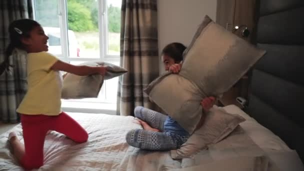 Slow motion of sisters having a pillow fight on a bed while away on their holiday.