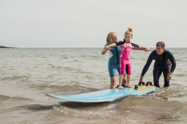 Parents teaching little girl how to surf at the beach. stock vector