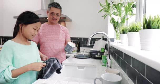 Malá holčička a její otec se dělá nádobí společně po rodinnou večeři