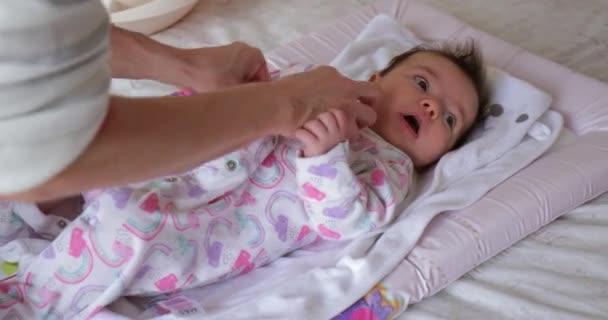 Holčička je oblečen v babygrow její matka
