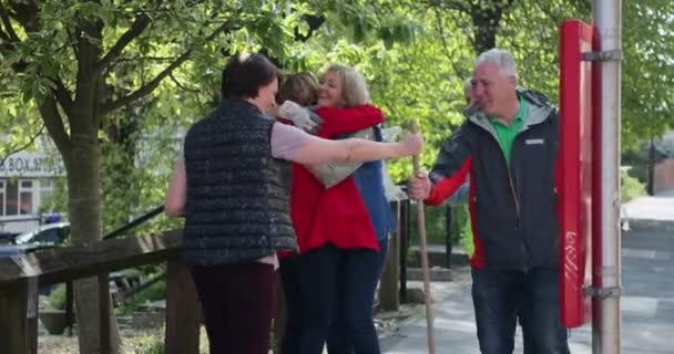 eine Gruppe von fünf reifen Erwachsenen, die sich umarmen, während sie sich im Freien begrüßen.