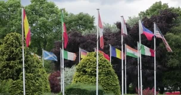 Zászlók a világ minden tájáról zászlórudakon, fúj a szél.