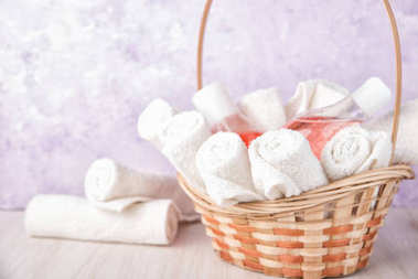 Rolled up white spa towels in a basket.