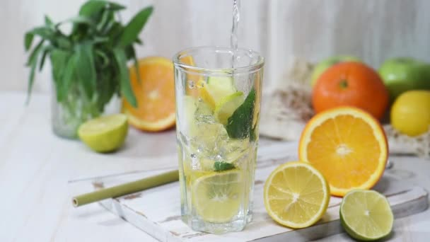 Pouring citrus lemonade into a glass with ice cubes. Fruit water, summer beverage on a wooden table