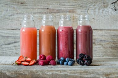 Selection of berry smoothies on rustic wood background