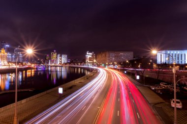 Moving car with blur light through city at night near Moscow riv