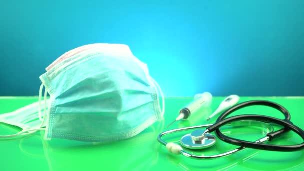 Coronavirus oder Covid-19 Medizinische Maske mit Stethoskop, elektronischem Thermometer und Spritze auf dem Tisch