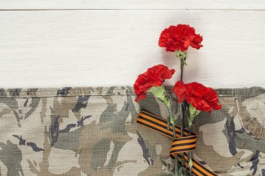 Red carnations with st george ribbons on the khaki background.