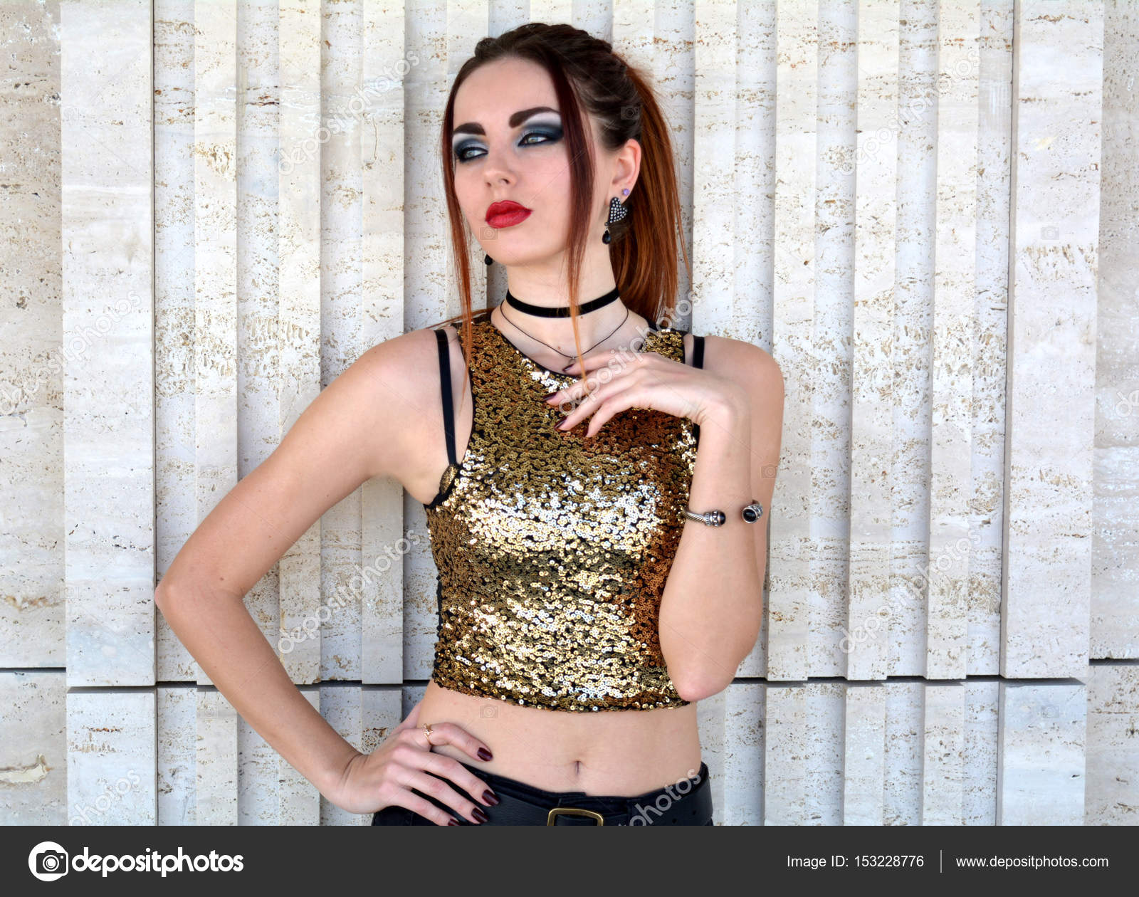 Portrait of young sad woman wearing gold top and posing by the white wall —  Stock 55b5dbffd8cf