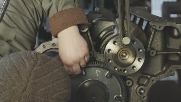 Mechanik práce s dieselovým motorem. Opravy motorů zblízka. V rukou nástroje.