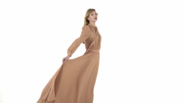 Modelka v létání béžové šaty.