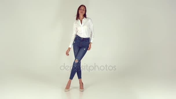 Mladá a veselá dívka v stylové džíny na bílém pozadí