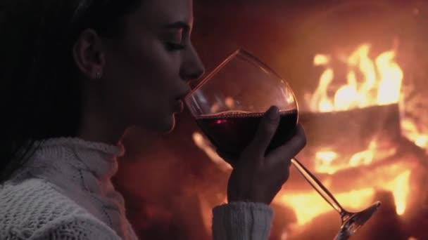 junge Frau sitzt zu Hause am Kamin und trinkt einen Rotwein.