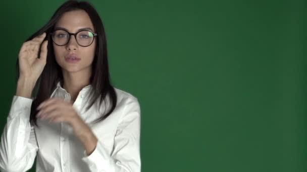 Mladá kráska žena v brýlích. Žena v kulaté brýle na světle zeleném pozadí zpomalené nahrávání