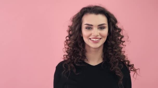 Gyönyörű divatos lány egy fekete póló hosszú göndör haj. Lány a stúdióban, a rózsaszín háttér. Reklám, hajápolási termékek, kozmetika, kozmetikai termékek, ruházat. Divat, boutique. Rózsaszín.