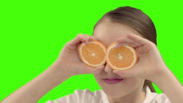 šťastná dívka drží polovinu Orange poblíž obličej