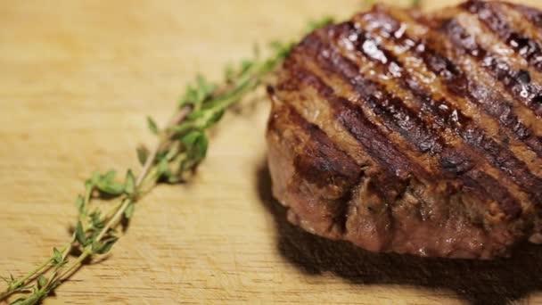 Detailní záběr na grilovaný steak na dřevěné desce