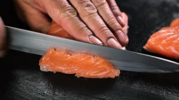 Férfi vágás vörös hal lazac fekete fedélzeten