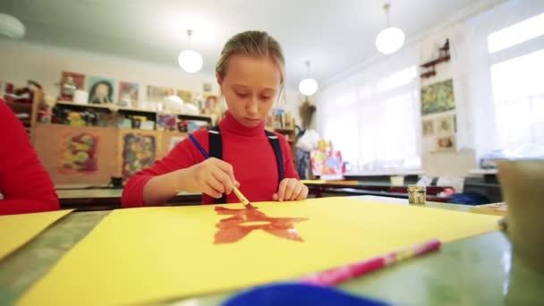 A lány felhívja egy képet fest az osztályteremben