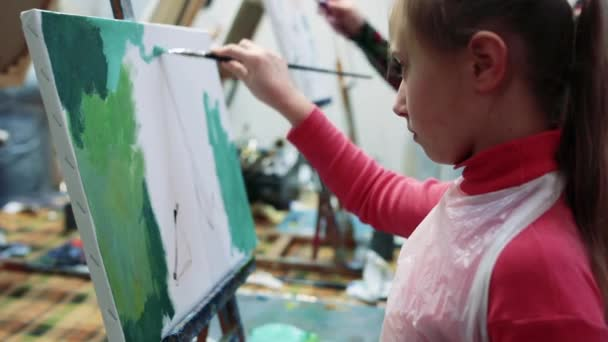 Artista della bambina pittura con olio su cavalletto.